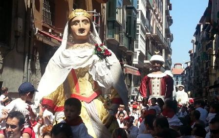 Giants of Pamplona dancing with people on the streets during the running of the bulls festival